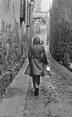 Adult, Adults, Alley, Alleys, Alone, B&W, Back view, Black-and-White, Contemporary, Daytime, Exterior, Female, Full-body, Full-length, Going away, Human, Lane, Lanes, Lifestyle, Lifestyles, Moving away, One, One person, Outdoor, Outdoors, Outside, People