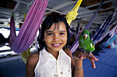 Little girl with parrot on the boat from Manaus to Belem. Amazon River. Brazil