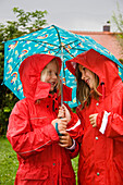 Two girls (6-7 years) wearing rainwear under an umbrella, Upper Bavaria, Germany