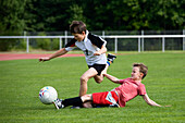 Two boys (7-8 years) playing soccer, Upper Bavaria, Germany
