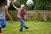 Children playing soccer in garden, Upper Bavaria, Germany