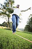 Young man balancing on rope, Irsee, Bavaria, Germany