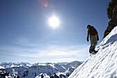 Snowboarder auf Abhang, dahinter Bergpanorama, Reutte, Tirol, Österreich