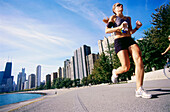 Young woman jogging, Gold Coast, Oak Street Beach, Chicago, Illinois, USA