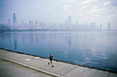 Young man jogging on shore of Lake Michigan, Northerly Island Park, Chicago, Illinois, USA
