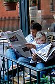 Couple reading newspaper in Café in Greenvich Village, Manhattan, New York, USA, America