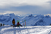 Two backcountry skiers resting on summit, Allgaeu Alps, Tyrol, Austria