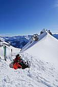 Zwei Skitourengeher bei Pause in Schneegrube, Woleggleskarspitze, Allgäuer Alpen, Allgäu, Tirol, Österreich
