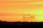 Delerict freighter: Greek freighter (Ithaca) stranded on Hudson Bay rocks in sunset fog. Churchill. Manitoba, Canada
