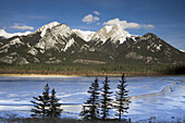 DeSmet Range reflected in open ice and water channel of Jasper Lake. Jasper National Park, Alberta, Canada