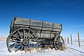 Antique hay wagon in snowy prairie. Alberta, Canada