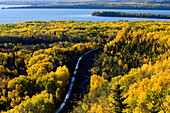 Aspen forest in autumn colour overlooking Lake Superior with rail line and train. Rossport. Ontario