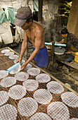 Man rolling out rice paper to dry as woman makes it. Don Teav, Battambang province. Cambodia.