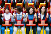 Action, Adult, Adults, Amusement, Amusement park, Amusement parks, Amusements, Blurred, Color, Colour, Contemporary, Danger, Daytime, Emotion, Emotions, Exciting, Exterior, Fair, Fairground, Fairs, Fast, Female, Fun, Funfair, Funfairs, Girl, Girls, Group
