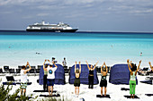 Aerobics class workout on the beach on Half Moon Cay with cruise ship in the background. Bahamas