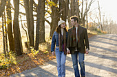 Couple walking on country road in autumn