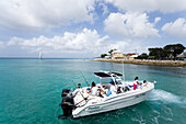 Persons in a motorboat near coast, Speightstown, Barbados, Caribbean