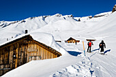 Skiers on slope passing alpine hut, First, Grindelwald, Bernese Oberland, Canton of Bern, Switzerland