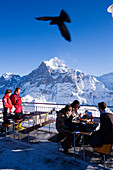 Guests on terrace of the mountain restaurant First, Wetterhorn in background, First, Grindelwald, Bernese Oberland, Canton of Bern, Switzerland