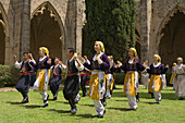 Local men and women in traditional costume dancing, folk dance, folklore, Bellapais Abbey, Beylerbeyi, Abbey de la Pais, monastery ruin, near Kyrenia, near Girne, North Cyprus, Cyprus