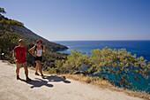 Ein Paar beim Wandern entlang der Küste, Küstenlandschaft mit Kiefer, Akamas Naturpark, türkis blauen Meer, South Cyprus, Cyprus