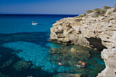 A group of young people bathing in the sea, coastal landscape with cave, boat, Akamas nature park, Cyprus