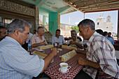 Local men sitting in a cafe playing a game, Kafenion, Dipkarpaz, Rizokarpaso, Karpasia, Karpass Peninsula, Cyprus