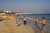 Four young men playing ball on the beach, Agia Napa, South Cyprus, Cyprus
