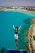 A young woman bungee jumping near Nissi Beach, Napa Bungee, Agia Napa, South Cyprus, Cyprus