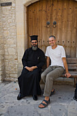 Father Neofytos, Orthodox priest, with photographer Juergen Richter in front of a monastery, Omodos, Troodos mountains, Cyprus