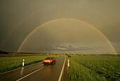 Rainbow over a country road near Glonn, Upper Bavaria, Bavaria, Germany