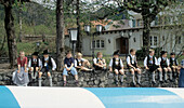 Kinder sitzen auf einer Mauer, Maibaum liegt im Vordergraund, Bayern, Deutschland