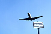 Airplane against blue sky, keep off sign in foreground, Berlin, Germany