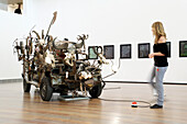 Young woman looking at a sculpture in the Jean Tinguely Museum, Basel, Switzerland