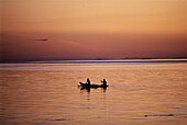 Two people rowing an outrigger canoe at sunset