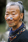 Apatani woman with traditional wooden plates (Hulos), tatoo and necklace. Arunachal Pradesh. India