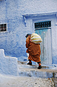 Woman in typical street in Chefchaouen, Morocco.