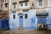Fountain and houses façades in Chefchaouen. Morocco