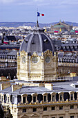 Aerial view of the domed Tribunal de Commerce with French flag and Garnier Opéra in the background. Paris. France