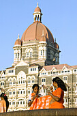 Women getting dressed in saris in front of the Taj Mahal Palace & Tower. Mumbai (ex Bombay). India