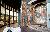 Priest showing religious fresco dating 18th century in Ura Kidane Mehret church. Zeghe peninsula, Tana Lake. Gondar province, Ethiopia