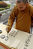Monk writing in a decorative hand at great wild goose pagoda or Dayanta. Xi an city. Shaanxi province. China.