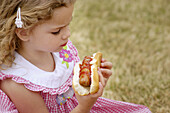 4 year old eating hot dog at event in private club park.