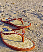 Accessories, Accessory, Beach, Beaches, Close up, Close-up, Closeup, Color, Colour, Comfort, Comfortable, Concept, Concepts, Daytime, Exterior, Holiday, Holidays, Leisure, Object, Objects, Outdoor, Outdoors, Outside, Pair, Pairs, Red, Sand, Sandal, Sanda