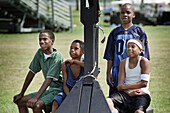 Four 12 year old black youths wait turn to play basketball