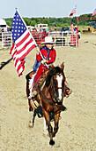 Teen female flag bearer in opening ceremonies of rodeo