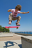 Teenage males perform jumping maneuvers on a skateboard in a public park