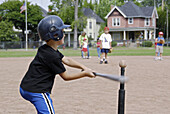 5 to 7 year old Children get their first experience playing baseball from a T.