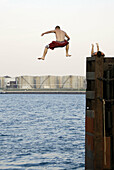 Teenage boy jumps and dives off of a high piling into a river