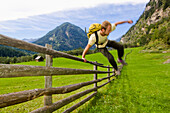 Hiker jumping over a fence, Malta Valley, Hohe Tauern National Park, Carinthia, Austria
